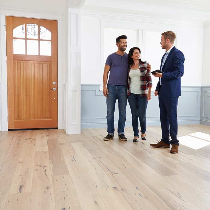 Home page image of a couple standing inside of a room with a realtor. Denver area real estate.
